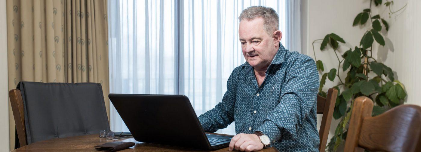Iets oudere man achter een laptop