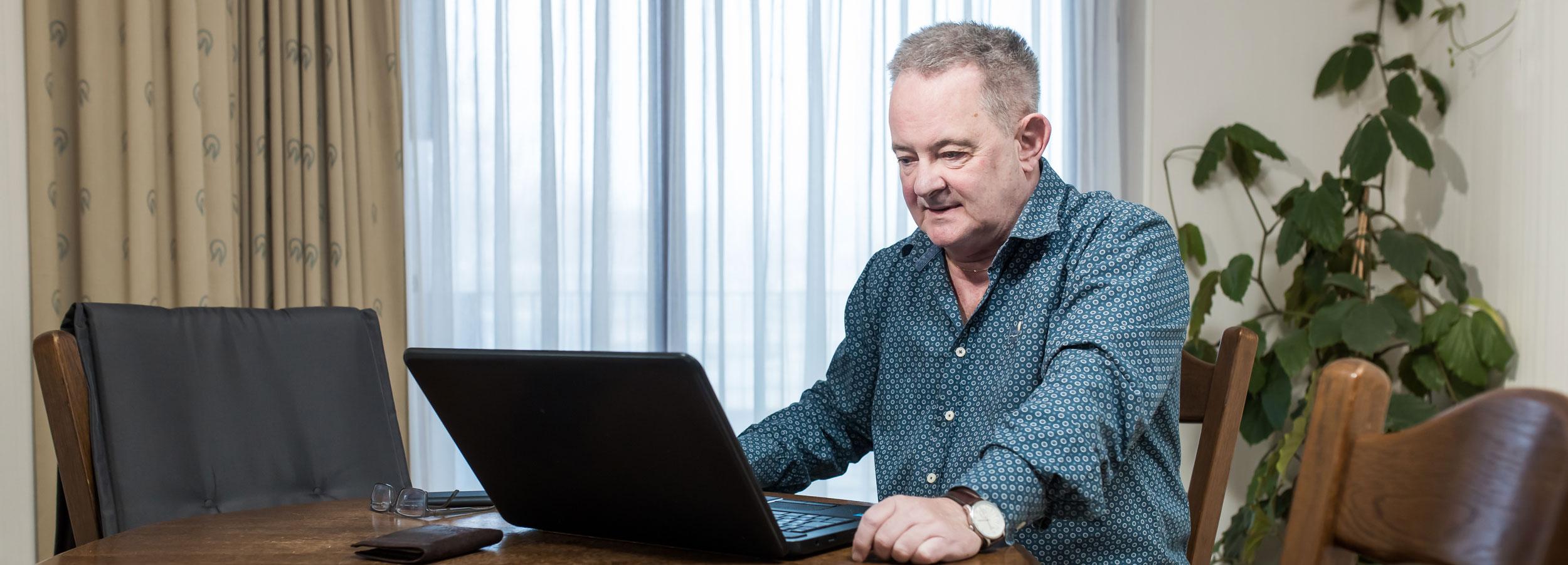 man achter een laptop