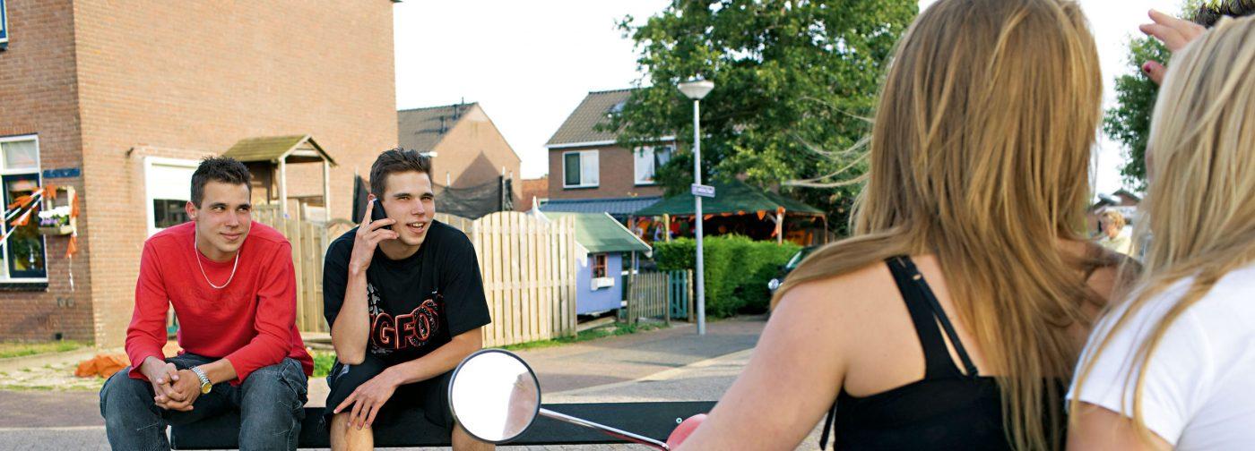Jongeren buiten op bank en scooter