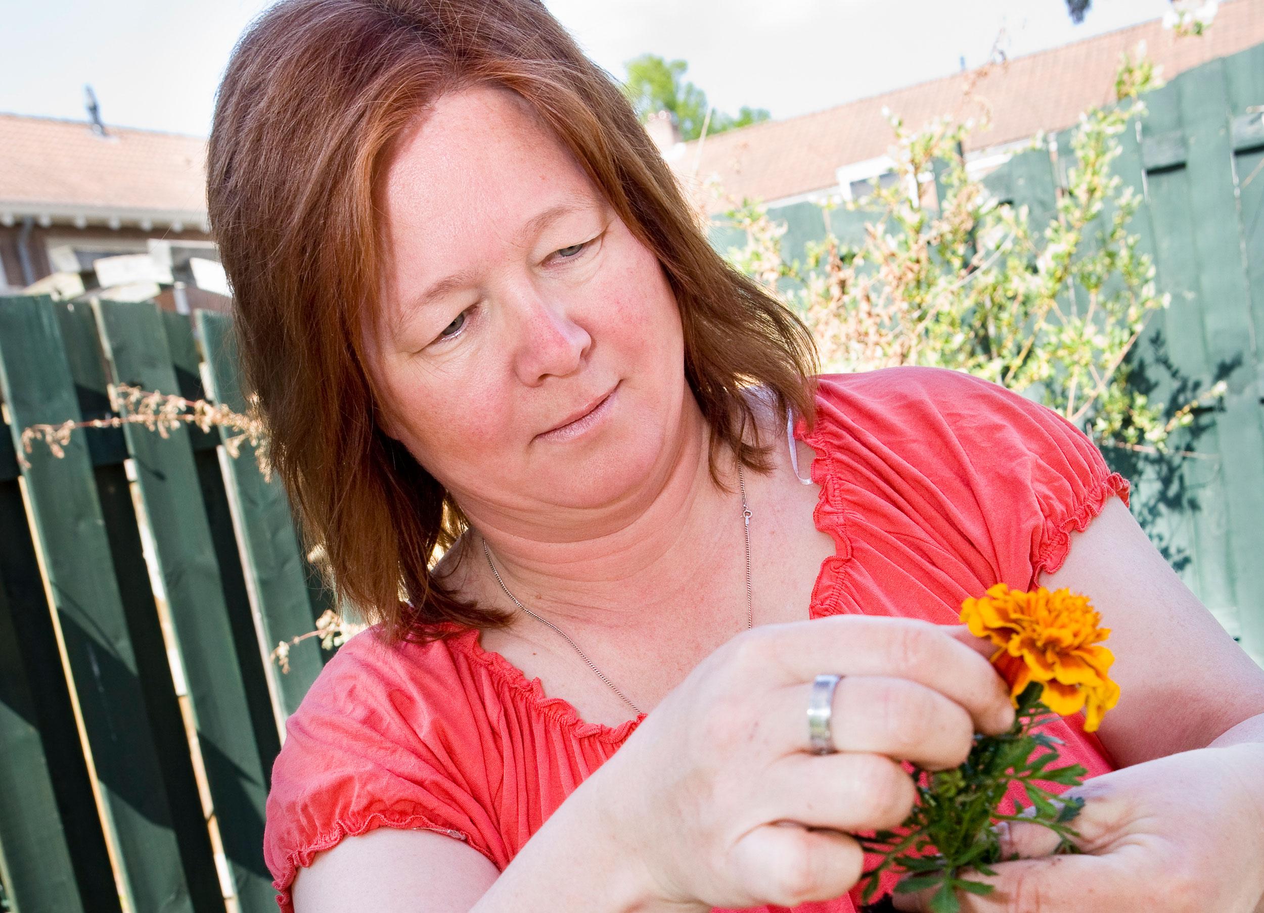 vrouw in de tuin met planten bezig