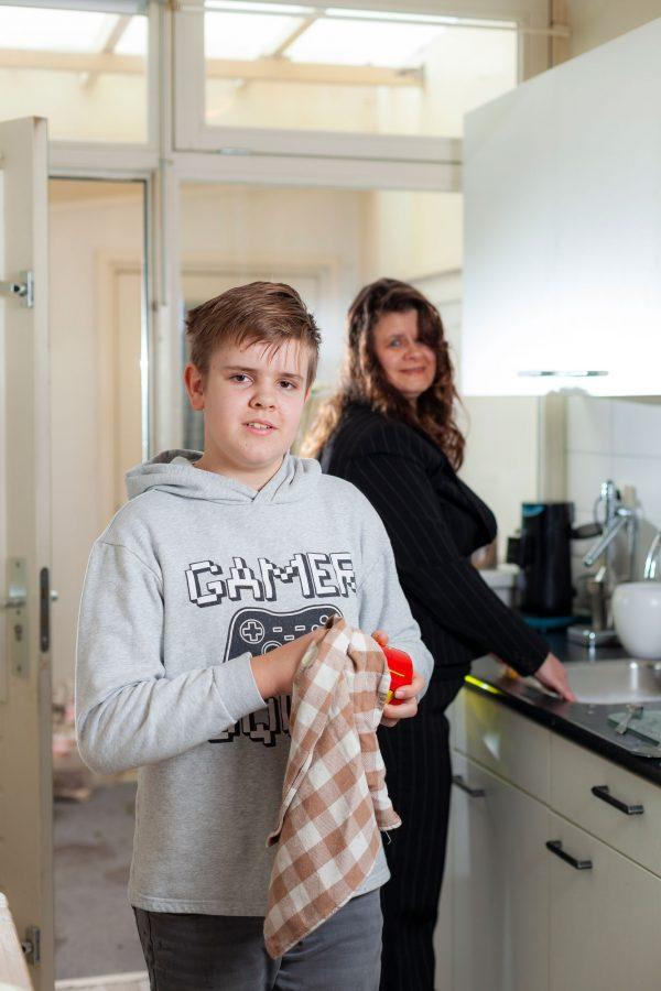 Moeder en zoon aan de afwas